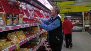 Monica Nurmi-Sinisalo limmar röda lappar på köttpaket i butiken