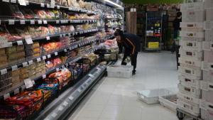 Ett butiksbiträde plockar in mat i butikshyllorna