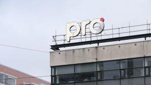 """En skylt med texten """"pro"""" ovanför på toggen av ett flervåningshus i stadsmiljö."""