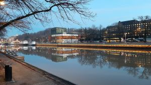 Åbo stadsteater och statens ämbetshus speglas i Aura å.