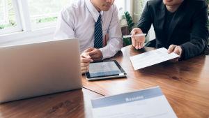 Två personer som vara syns från nacken nedåt diskuterar vid ett bord. De har papper och en pekdator i händerna.