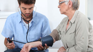 En man mäter blodtrycket på en äldre kvinna.