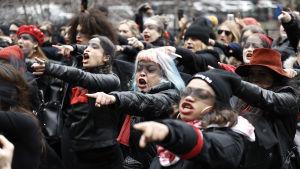 Kvinnor i svarta kläder pekar och skriker.