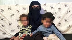 En norsk terrormistänkt kvinna och hennes två barn sitter tätt ihop. Barnens ansikten är blurrade.