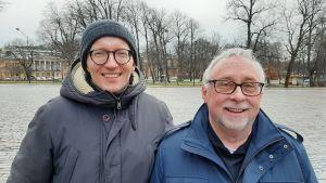 Christopher Skutela och Stephen Person, två glada män med glasögon turistar i Åbo, med Åbo Akademis huvudbyggnad i bakgrunden.