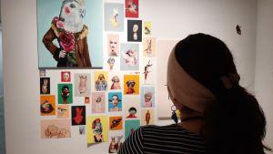 Bessie Reyes, en dam med hästsvans och gult band kring håret, står och tittar på konst på en utställning.
