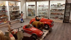 Musse Pigg, röda trampbilar och andra leksaker på ett leksaksmuseum.