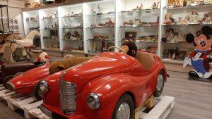 En stor röd trampbil mitt på golvet bland en stor mängd leksaker i ett leksaksmuseum.