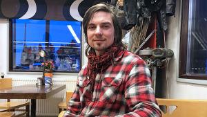 Fredrik Aspö med en kopp kaffe vid en grill i Sibbo.