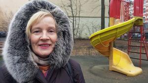 Valentina Lopatina står på en lekplats framför en rutschkana.