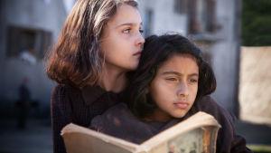 Kaksi tyttöä lukee kirjaa