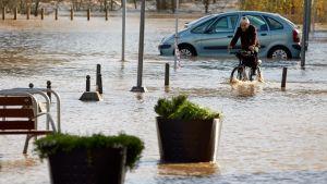 En man cyklar på en översvämmad gata i Sant Ponc. En bil med vatten upp till halva hjulen i bakgrunden.