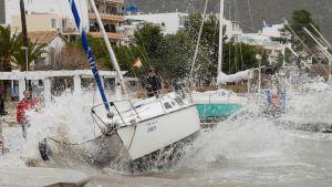 En våg slänger upp en segelbåt mot strandpromenaden på Mallorca.
