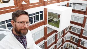 Nikolas Salomaa, en man med glasögon, mustasch och skägg, står på en balkong mellan höga hus.