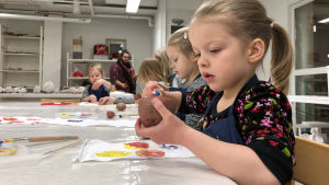 Kuvassa lapsi maalaa perunaa ja painaa perunalla kankaaseen kuvan