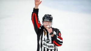 Jarno Heikkinen håller ett papper för munnen
