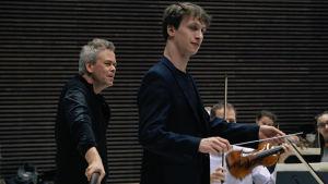 Närbild på Hannu Lintu och James Kahane då Kahane dirigerar.