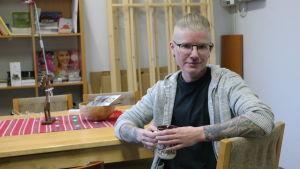 Alexander Rancken sitter vid ett bord med en tekopp i handen