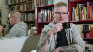 Alexander Rancken sitter framför en bokhylla i Åbo bokcafé, bakom honom en spegel som visar honom i profil