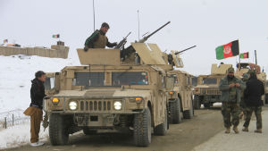 En konvoj med militärfordon, några män står intill bilarna.