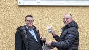 Roihuvuoriseuran toiminnanjohtaja Otto-Ville Mikkelä ja toimittaja Jukka Mikkola arpomassa DDR-kisan voittajaa