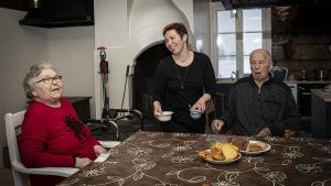 Keskellä kuvaa on Vuokko Lahti, joka korjaa astioita pöydästä. Hänen molemmilla puolillaan istuu vanhus pöydässä.