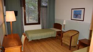 Rum med sängar, bord, fotölj och stol