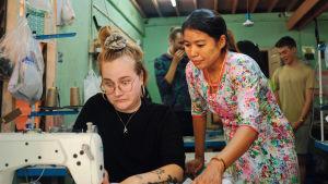Nuori suomalainen nainen kauhistuneen näköisenä kokeilee ompelukonetta Myanmarissa vaatetahtaalla. Paikallinen nainen opettaa.