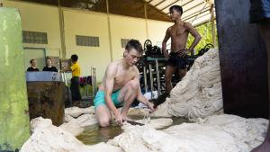 Nuori suomalainen mies käsittelee puuvillaa pienellä tehtaalla Myanmarissa.