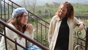 Kaksi naista istuvat portailla kauniissa maisemassa ja hymyilevät.