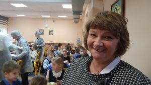 En leende kvinna framför barn som äter skolmat.