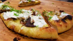 Kotitehty pizza leikkuulaudalla.