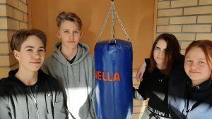 Juhana Virkkunen, Georg Sarlin, Julia Adolfsson och Olga Åberg, fyra ungdomar från Nagu står kring en boxningssäck.