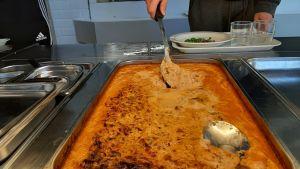 En sked sticks ner i en stor form med orange brolierpasta i en skolmatsal.