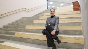 Sivistysjohtaja Sari Gustafsson istuu uuden Strömborgska skolanin rappusilla.