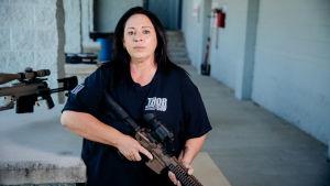 Nainen aseen kanssa katsoo suoraan kameraan.