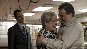 Watson Bryant (Sam Rockwell) ser bekymrad ut då Bobi Jewell (Kathy Bates) gråter och Richard Jewell (Paul Walter Hauser) håller om henne.