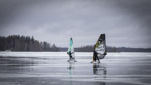 Kaksi talvipurjehtijaa Lestijärven jäällä.