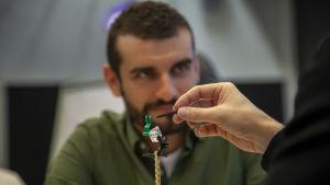 En man i bakrunden lyssnar på en presentation av en legomodell i förgrunden.