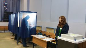 Vallokal i Ryssland. En frivillig står vid ett bord och tittar åt sidan medan man ser en man stå i ett bås och rösta.
