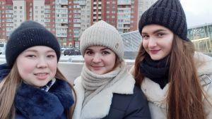 Tre unga vinterklädda kvinnor ler blygt mot kameran.