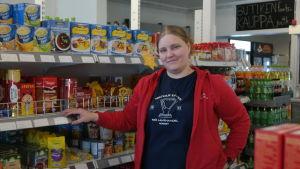 Jessica Blomqvist står framför en hylla med varor i sin butik Iniö Lanthadel