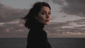 Ruskeahiuksinen laulaja Behm siesoo sivuttain pilvisen merimaiseman edessä ja katsoo suoraan kameraann sivulleen. Kuvan sävy on punertava.