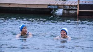 Två glada kvinnor med mössa på huvudet simmar