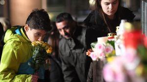 En pojke kysser rosorna innan han lägger ner dem på en minnesplats.