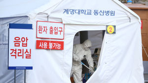Ett vitt tält där en person i vit overall står i öppningen med ett skaft i handen. Tältet är en tillfällig karantän för coronavirussmittade i Sydkorea.