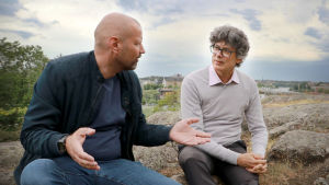 Kaksi miestä istuu kallioilla ja keskustelee