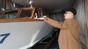 Björn Fritzén står bredvid sin gamla lackerade träbåt