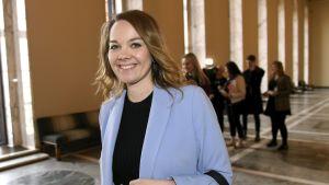 Katri Kulmuni har blont hår och en ljusblå kavaj och tittar leende in i kameran samtidigt som det ser ut som att hon är påväg någonstans.