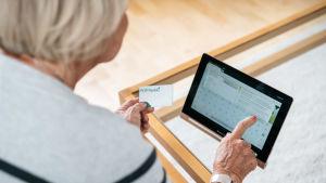 En äldre dam som loggar in på sin nätbank